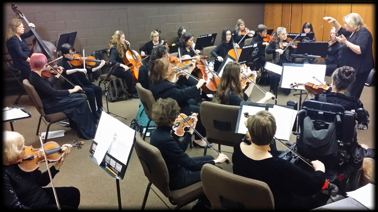 Image of WOA Women's Orchestra of Arizona musicians rehearsing with Cindy H. Petty conducting.