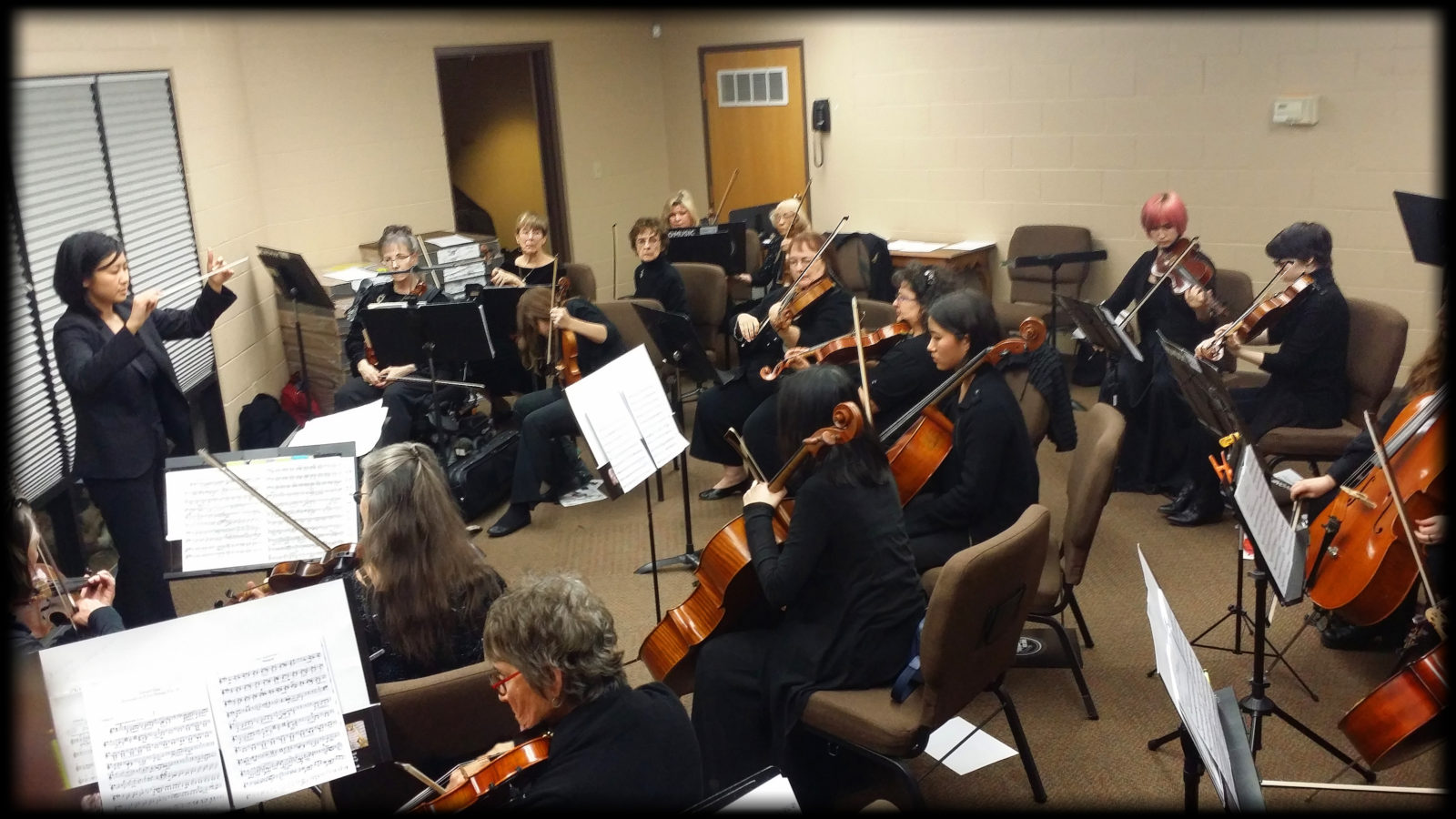 Image of WOA Women's Orchestra of Arizona musicians rehearsing with Livia Gho conducting.